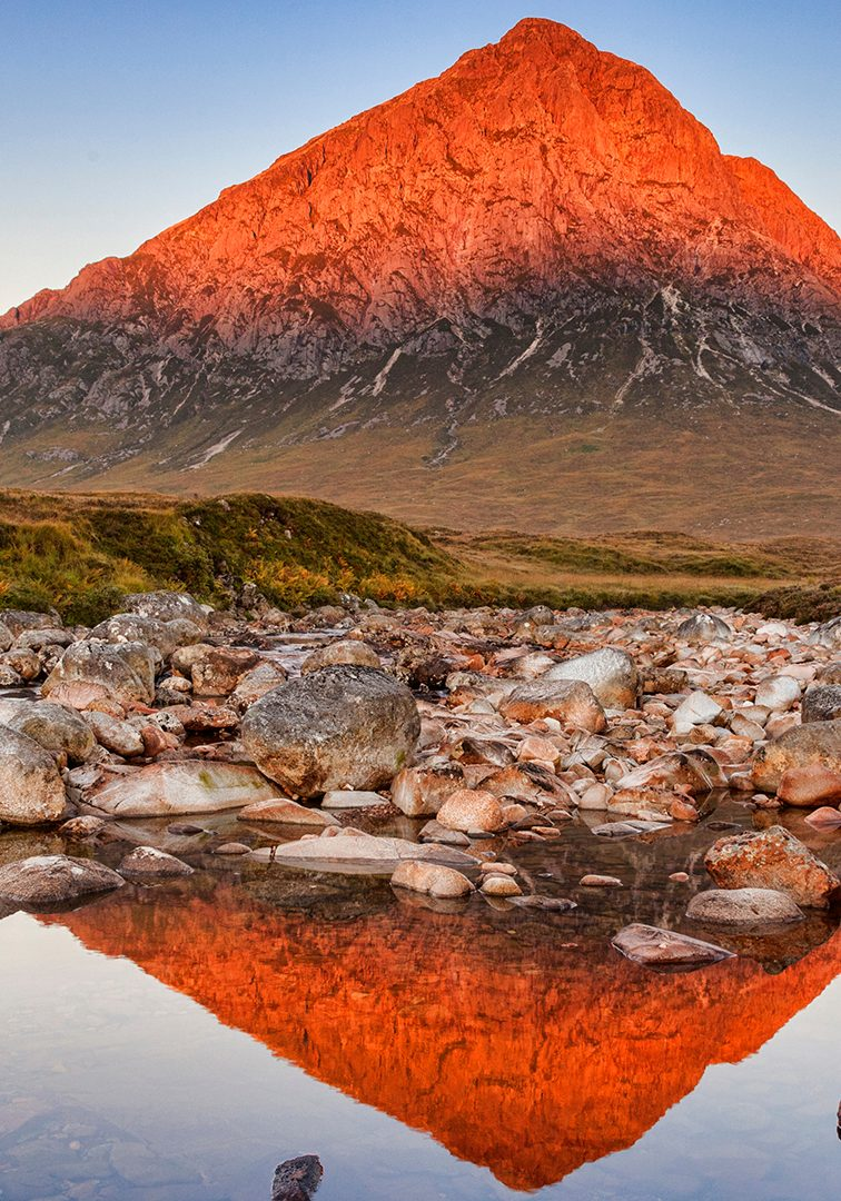 Peak in Scotland turned red by sun reflected in a river